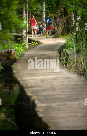 A tourist family strolling on a wooden pontoon (Plitvice Lakes National Park - Croatia). Holidaymakers on a wooden - Stock Photo