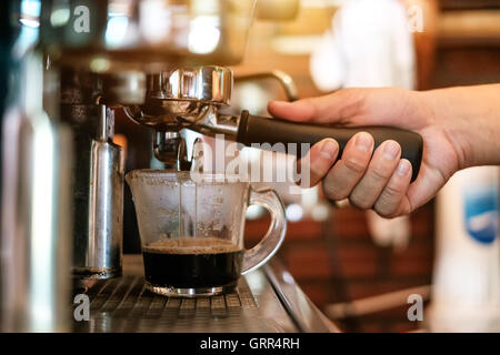 Cup and professional espresso machine pouring fresh coffee into a ceramic cup - Stock Photo