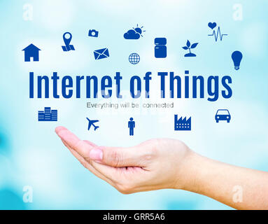Open hand with Internet of Things (IoT) word and icon on blue blur background, Technology concept. - Stock Photo