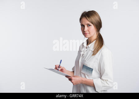 Cheerful medical doctor woman taking notes. Isolated on white - Stock Photo