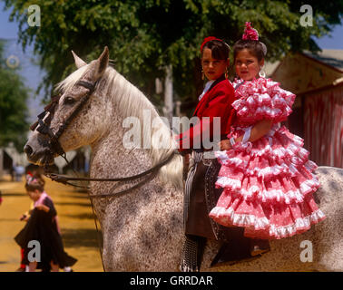 Spanish girls in National dress at the Feria (Horse Fair) in Seville, Andalucia, Spain - Stock Photo