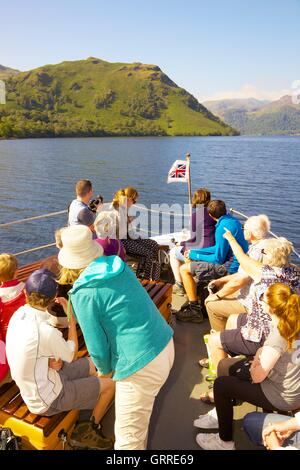 Tourists enjoying a cruise aboard the bow of Ullswater Steamers. Ullswater, Penrith, The Lake District National - Stock Photo