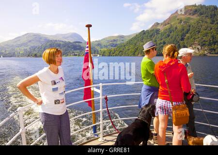 Tourists with their dogs enjoying a cruise aboard the stern of Ullswater Steamers. Ullswater, Penrith, The Lake - Stock Photo