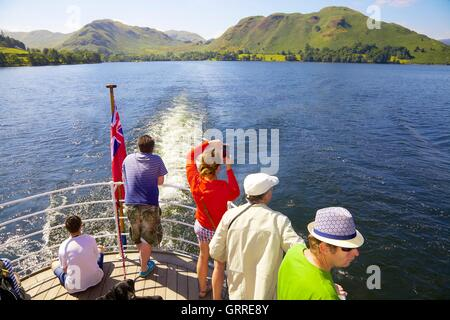 Tourists enjoying a cruise  and taking photographs aboard the stern of Ullswater Steamers. Ullswater, Penrith, The - Stock Photo