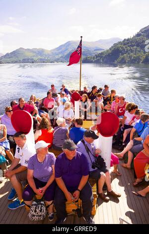 Tourists enjoying a cruise aboard the stern of Ullswater Steamers  M Y Raven. Ullswater, Penrith, The Lake District, - Stock Photo