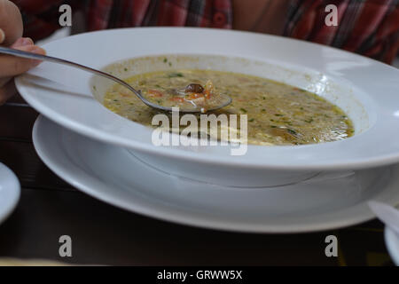 Woman's hand with the spoon while eating soup in the restaurant - Stock Photo