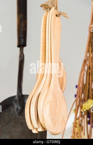 wooden spoons hanging with rope in kitchen - Stock Photo