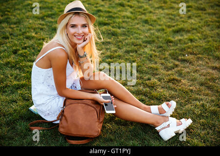 Cheerful pretty young woman with backpack sitting on grass and listening to music with cell phone - Stock Photo