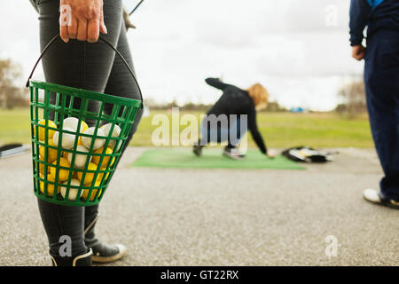 Low section of woman holding basket with balls at golf course - Stock Photo