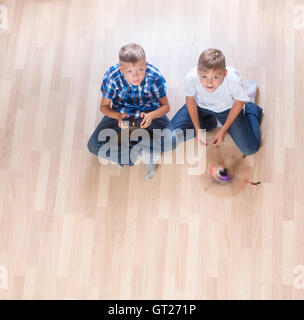 kids playing with flying helicopter model at home using remote control - Stock Photo