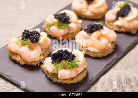 Shrimp Appetizer served on toasted bread and served on a slate plate - Stock Photo
