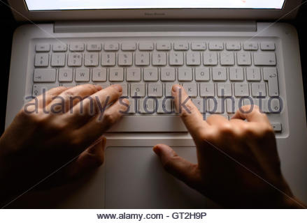 File photo dated 06/08/13 of someone using a laptop keyboard. Innocent people have been caught up in criminal investigations - Stock Photo