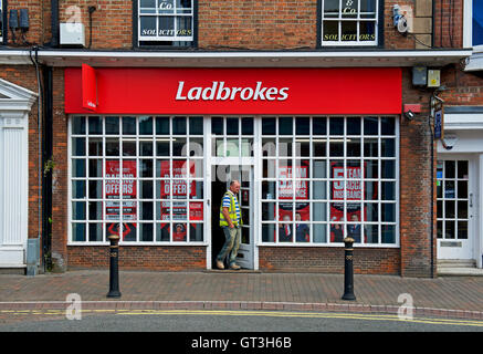 Man leaving Ladbrokes betting shop, England UK - Stock Photo