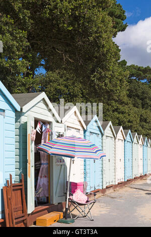Parasol and beach huts on a warm sunny day at Avon Beach, Dorset in September - Stock Photo