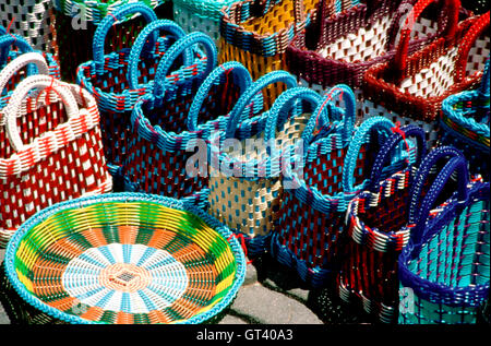 Stacks of colorful handmade woven baskets on display at a Mexican market in the Zocalo of Oaxaca, Mexico. - Stock Photo