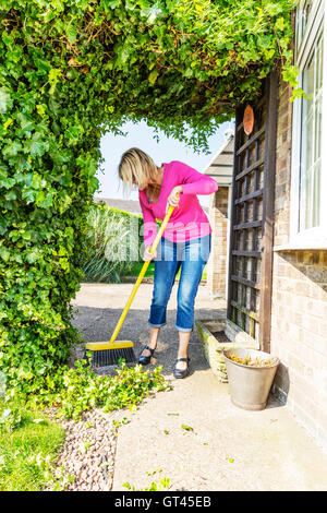 sweeping up mess broom brushing sweep gardening gardener hedge cuttings UK England GB - Stock Photo