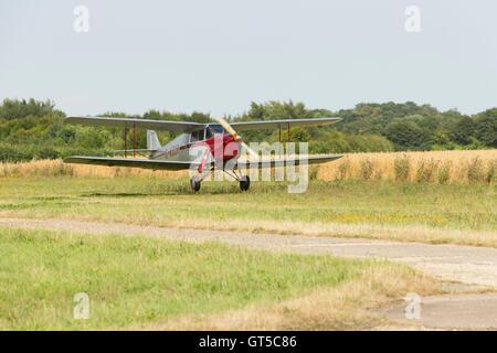 De Havilland Hornet Moth bi plane G-ADUR landing on grass airstrip airfield. Unsharpened - Stock Photo