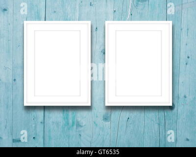 Close-up of two blank picture frames on aqua weathered wooden boards background - Stock Photo