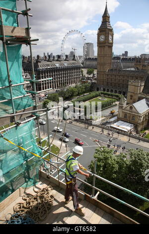 A young scaffolder works on Westminster Abbey overlooking Big Ben, Parliament Square and the London Eye - Stock Photo