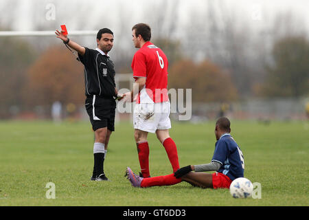 A Hackney Os player is sent off - Hackney Os (red) vs Birkbeck Orient (blue) - Hackney & Leyton Sunday League Football - Stock Photo