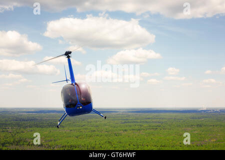 The aircraft - the small blue helicopter flight against the background of the cloudy sky. - Stock Photo