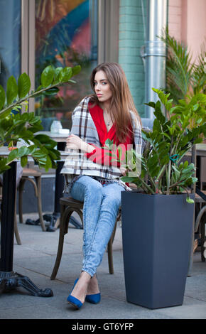 Young beautiful brunette girl sits in summer cafe in the street wrapped blanket - Stock Photo