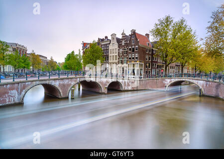 Amsterdam. Bridge and water canal. Boat light trail in long exposure on sunset. Holland or Netherlands. Europe. - Stock Photo