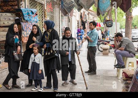 Women, men and children on the sidewalk in Yazd, Iran. - Stock Photo
