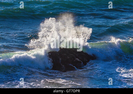 Wave breaking On Rocks Pacific Ocean - Stock Photo