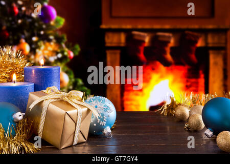 Christmas decorations, a gift and candles in front of a fireplace. A fire is burning in the fireplace and Christmas - Stock Photo
