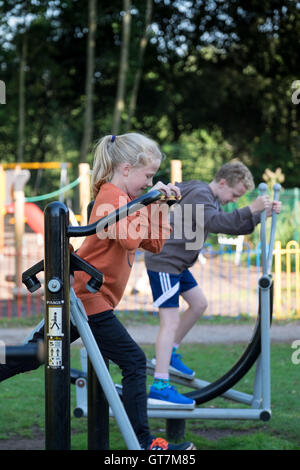 Two young children exercising on apparatus in a UK park - Stock Photo