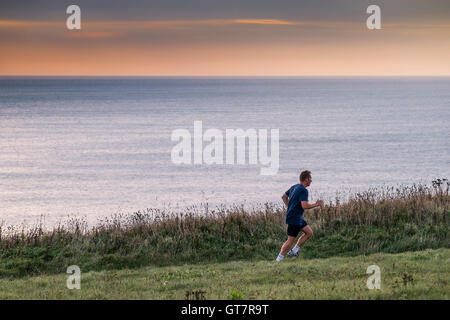 A man running along the South West Coastal Path between Newquay and watergate Bay in Cornwall. - Stock Photo