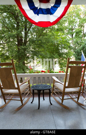Two Wooden Rocking Chairs with Small Table at the Terrace with Conceptual American Flag Fronting Tall Green Trees - Stock Photo