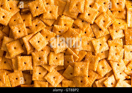 Background texture of square cheese crackers with central holes arranged in a layer viewed close up full frame from - Stock Photo