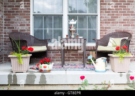 Wicker furniture on the patio with a samovar and tea cups ready for a relaxing tea break in the spring sunshine - Stock Photo
