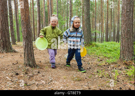 4 year old brother and sister walking with their frisbees through the woods, Sweden - Stock Photo