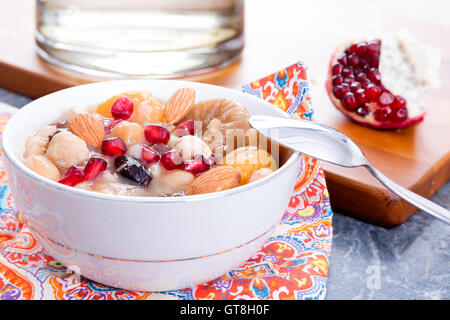 Turkish Noah's Pudding or ashure served with pomegranate and nuts in a white bowl on a colorful napkin for dessert - Stock Photo