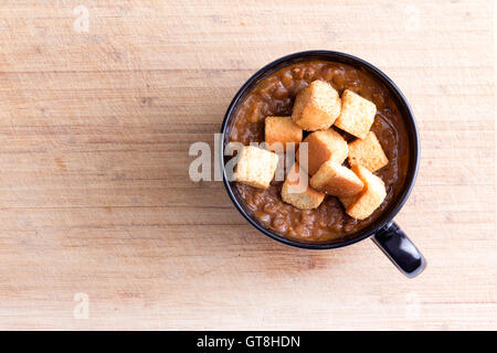 Single serving of scrumptious lentil soup garnished with toasted croutons in little bowl with handle on wooden table - Stock Photo