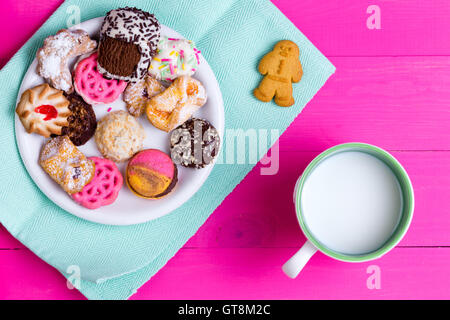 Selection of quality crunchy cookies on a plate served with a mug of farm fresh milk on an exotic bright pink picnic - Stock Photo