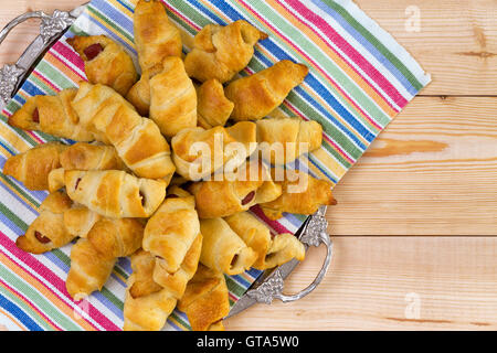 Heap of delicious fresh hot dog croissants on a colorful napkin and tray on a wooden picnic table for delicious finger food summ