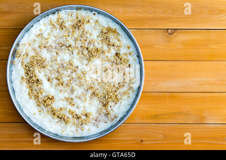 Speciality gullac Turkish dessert in round pan ready to serve viewed from above on a wooden table with copy space - Stock Photo