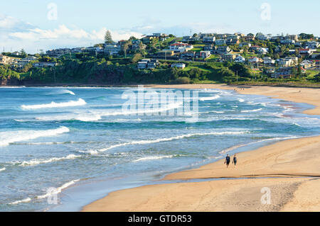 Two persons walking on Bombo Beach, Kiama, New South Wales, NSW, Australia - Stock Photo