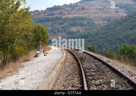 Woman without baggage waiting for a train at a small rural train station in a sunny summer day. - Stock Photo