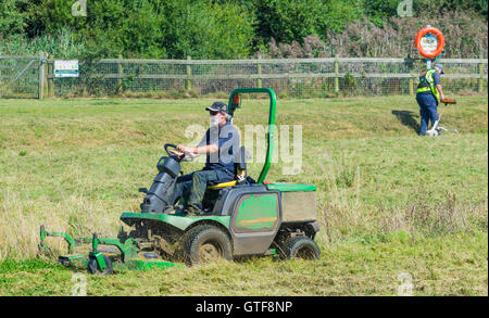 Man cutting grass in a park with a ride on lawnmower. - Stock Photo