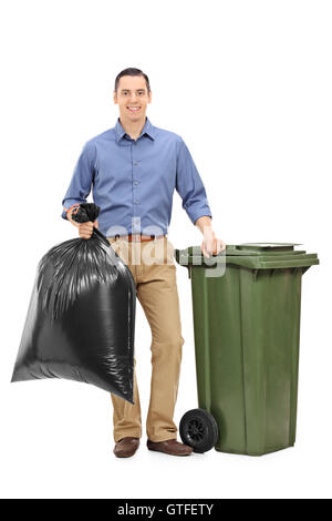 Young guy standing next to a garbage can and holding a trash bag isolated on white background - Stock Photo
