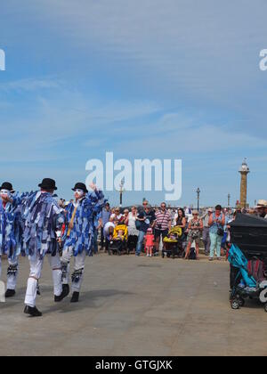 A crowd watch Hexham  Morris dancers performing on the quayside at Whitby Folk Festival 2016 - Stock Photo