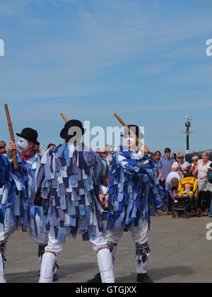 A crowd watch Hexham  Morris dancers performing on the quayside at Whitby Folk Festival 2016. - Stock Photo