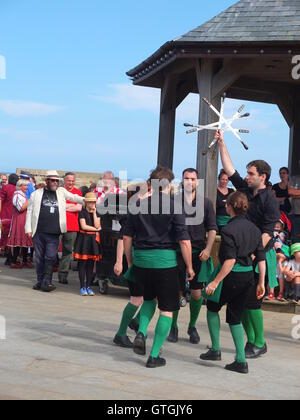 A crowd watch Four Corner Sword dancing troupe performing on the quayside at Whitby Folk Festival 2016. The 'lock' - Stock Photo