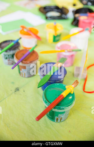 Pots of paint on a table with paintbrushes resting on top. Stock Photo