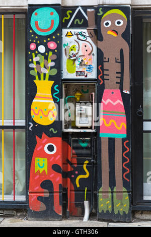 colourful mural street art graffiti surrounds gas meter at Shoreditch, London in September - Stock Photo